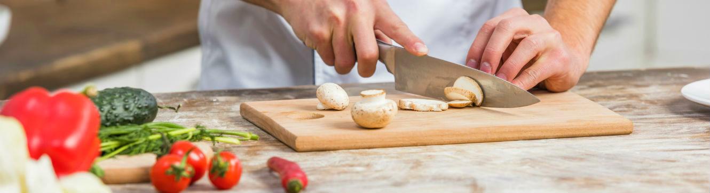 Un cuisinier émince des champignons