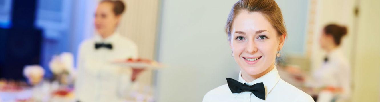 Une serveuse souriante dans un restaurant haut de gamme