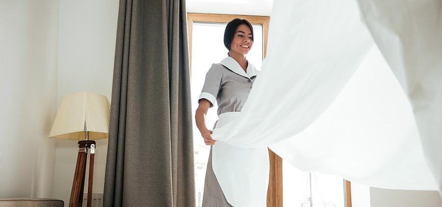 Une femme de chambre prépare un lit dans une chambre d'hôtel